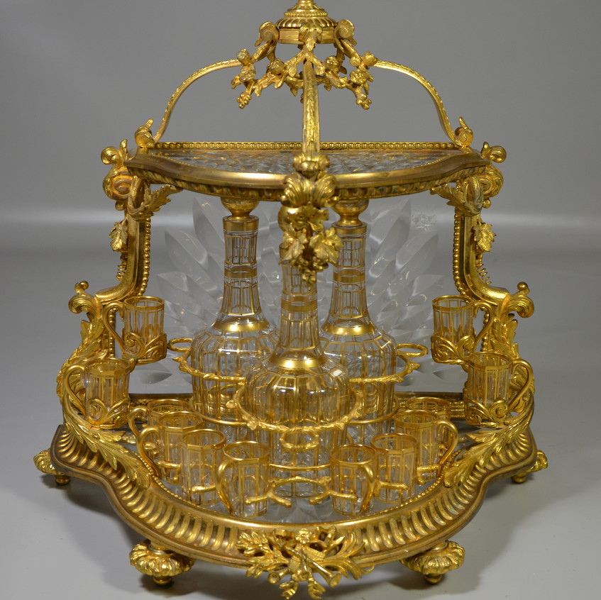 """French gilt bronze and crystal open tantalus, the ornate fire gilt frame fitted with scalloped faceted crystal panels for bottom, back, and hinged top, holding 3 gilt decorated crystal decanters and 12 liqueur glasses, 9 with handles, back stamped """"BREVETE / SGDG"""", 17"""" h, 17"""" w, 11 1/2"""" d, second half 19th c."""