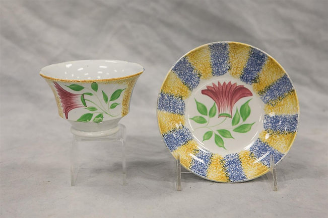 Blue and yellow rainbow spatter cup and saucer with thistle decoration