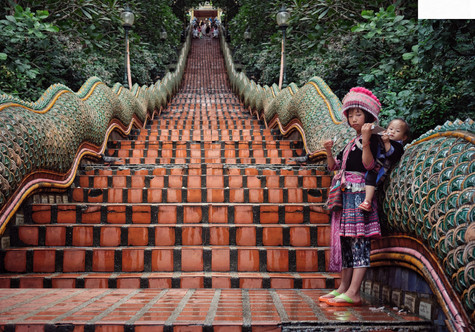 A young girl from Meo hill tribe is forced by her mother to panhandle each day at tourist-frequented Wat Doi Suthep // Chiang Mai Province, Thailand, 2018