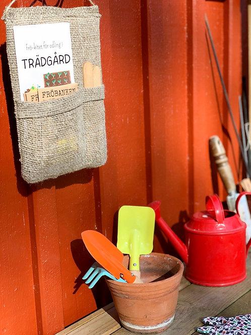 Odla med barn i trädgård - frön och märkpinnar i en praktisk väggförvaring