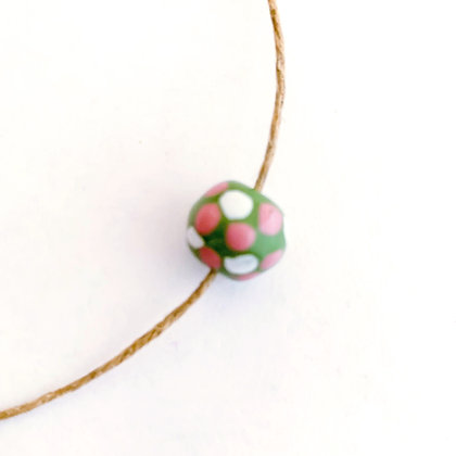 green with white and pink dots round ball