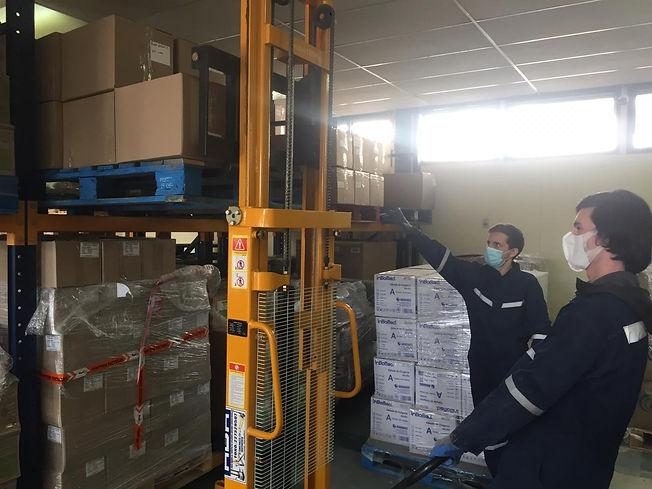 Imagen con dos personas utilizando una máquina para sacar varias cajas desde un estante