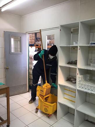 Imagen con una persona preparándose para trapear el piso en una fábrica