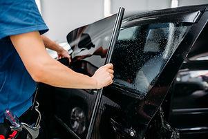 Male specialist applying car tinting fil