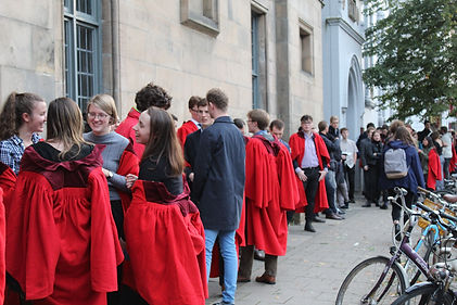 Students queuing. Some are in red gowns.