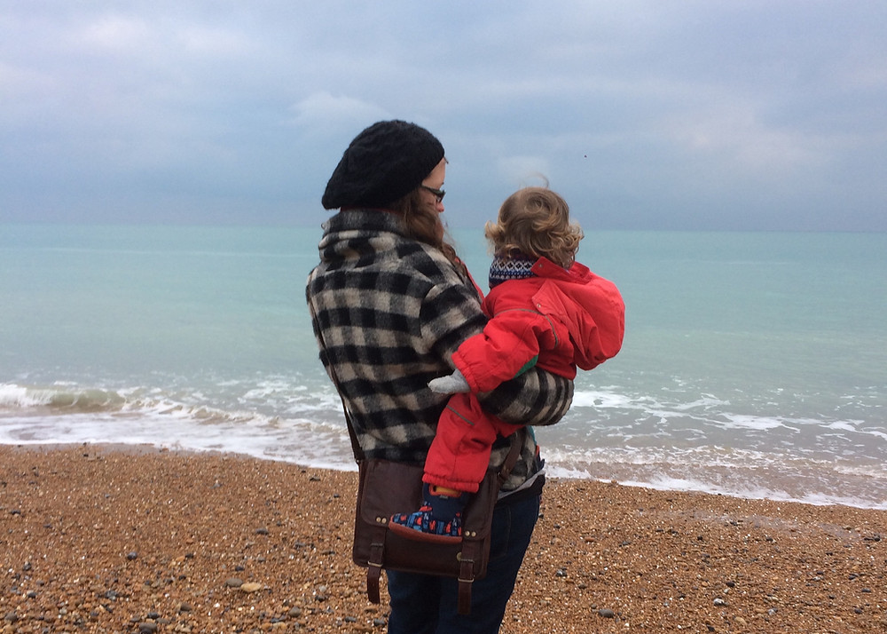 Beth wearing a black, white and grey chequered coat and a black hat. She has a brown handbag and is holding a toddler with curly hair wearing a red snow suit. They are on a pebbly beach overlooking the sea.