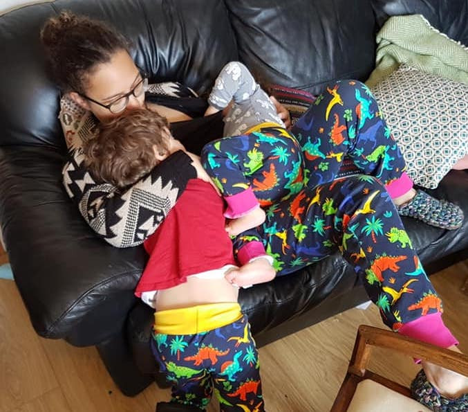 Ella with her children, all wearing matching dinosaur trousers.