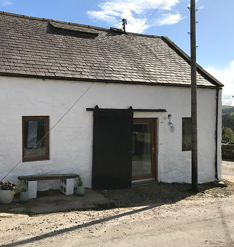 The front face of the rustic sotne build cottage, which is the camping barn/bothy at the open gate campsite