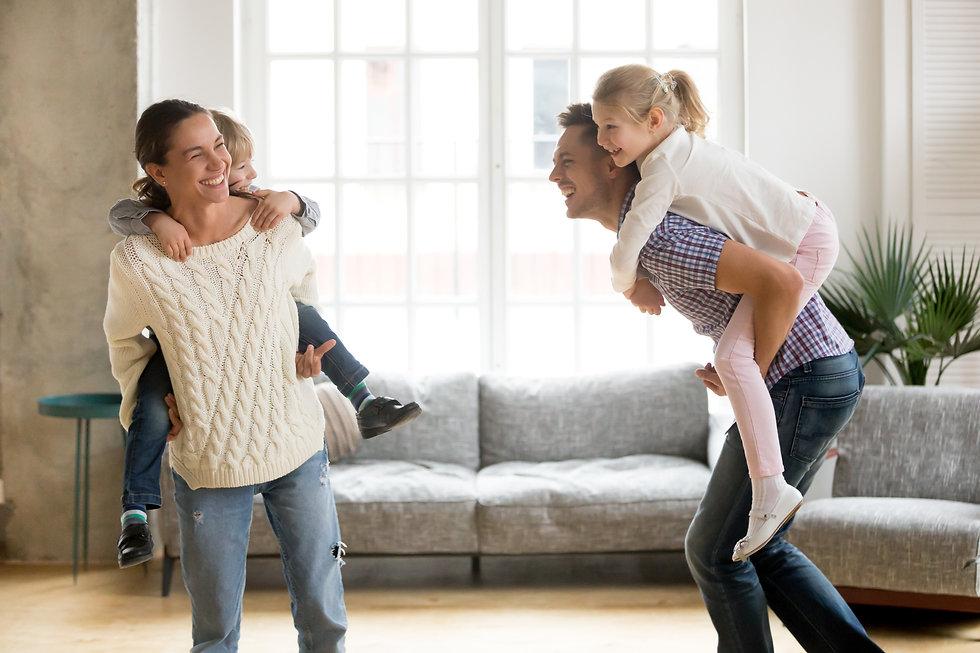 laughing-parents-giving-children-piggyba
