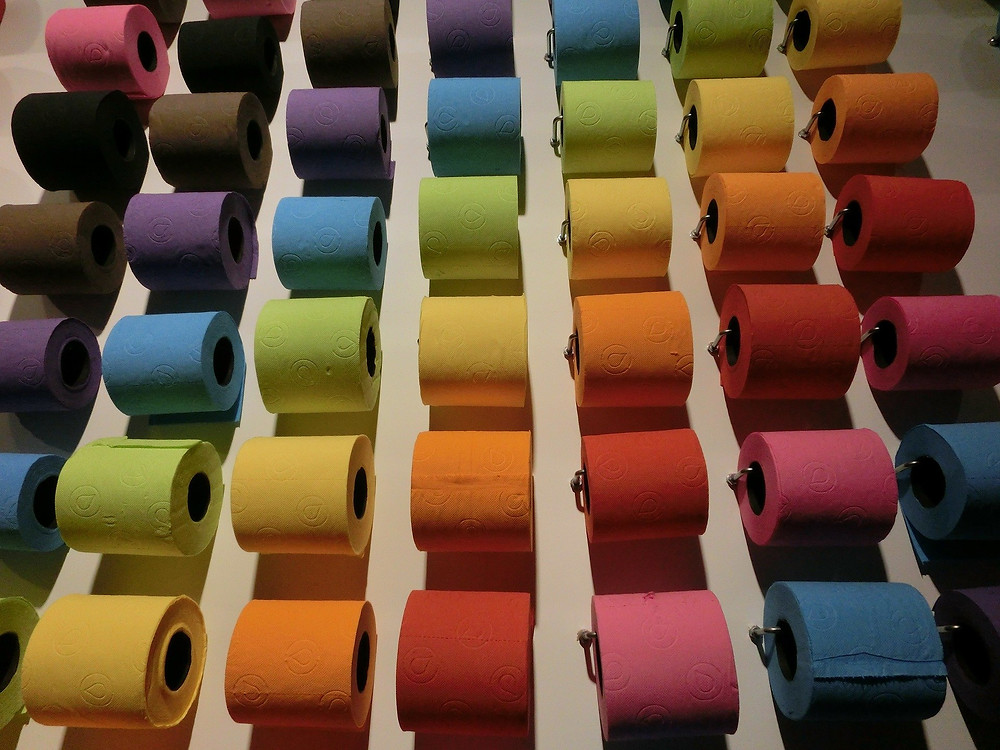 A wall of coloured toilet rolls that looks like a rainbow