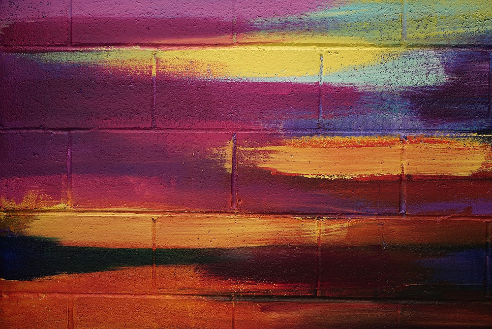 A close up of a brick wall painted in pinks, yellows, reds, blues and purples