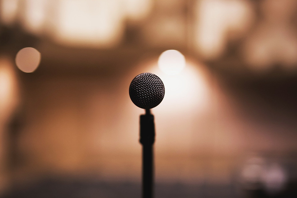 A microphone on a stand pointed directly at the viewer overlooking bright warm lights