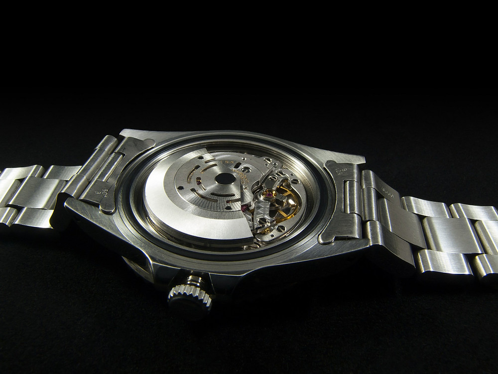 A stainless steel wristwatch lying face down with the back cover removed and some of the inner mechanism exposed