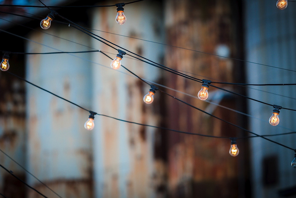Strings of illuminated light bulbs hang suspended over an outdoor space