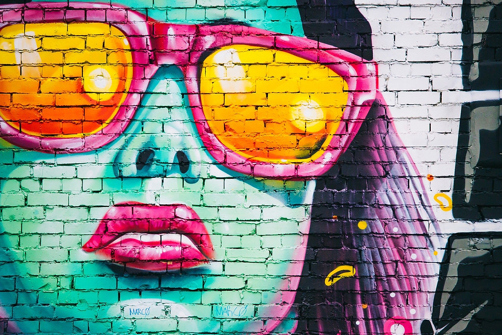 A graffiti art brick wall showing a woman's face up close and she's wearing sunglasses