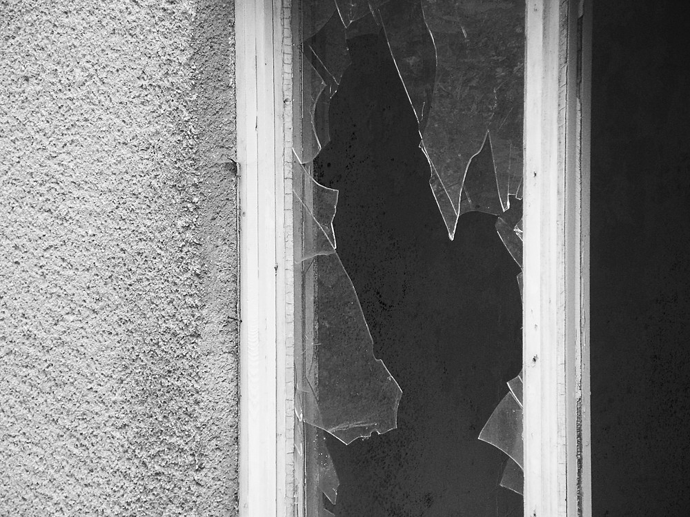 A concrete wall with a window of broken glass