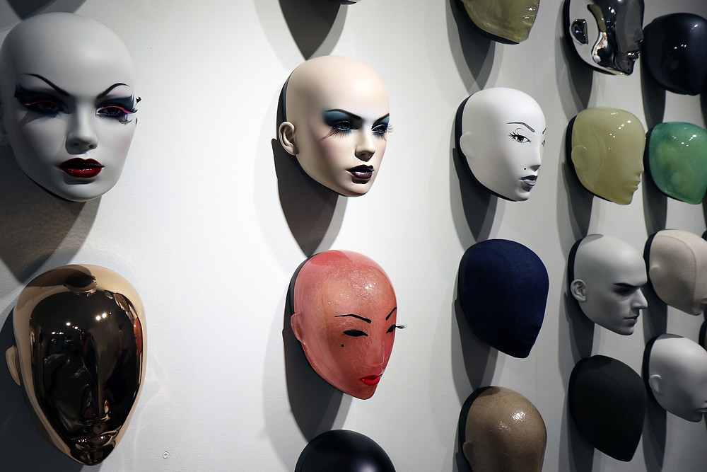 A wall of face masks in different colours and with different expressions