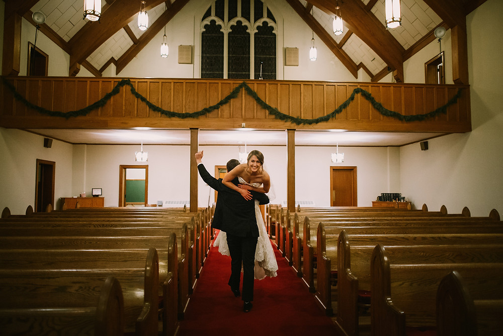 Groom carrying bride.