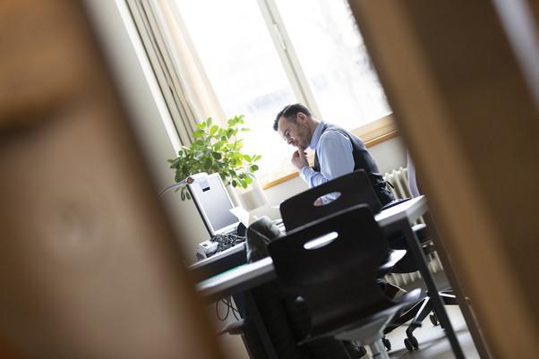 Imagebild für Allgemeine Berufsschule Zürich, Lehrer sitzt in Klassenzimmer und korrigiert Aufgaben der Schüler