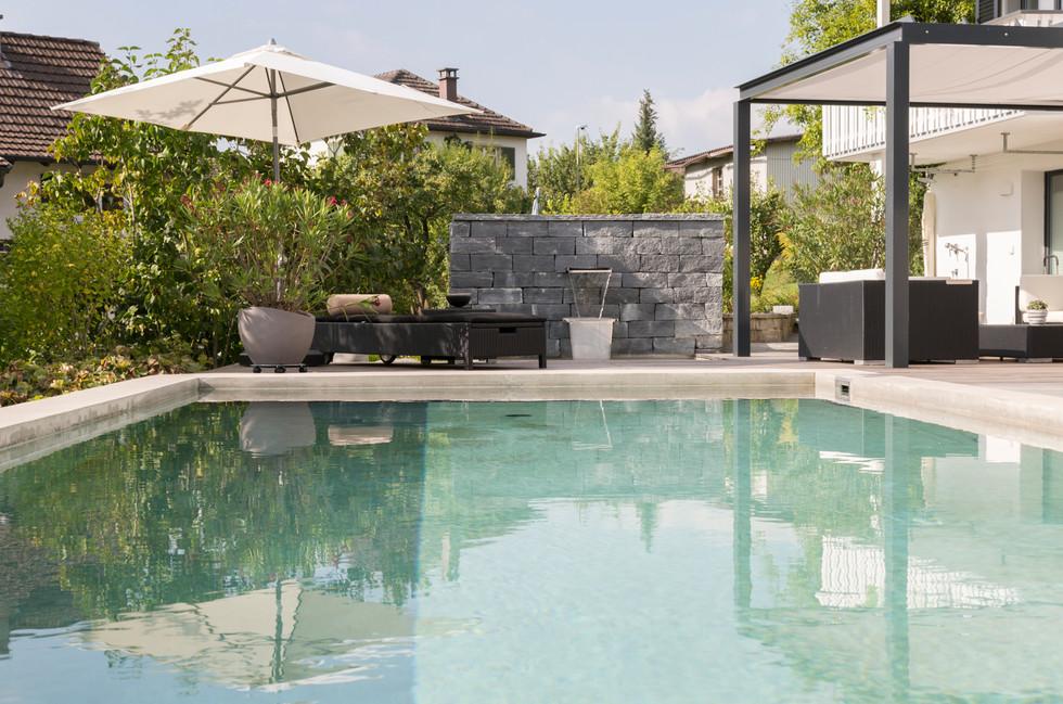 Pool und Garten, Sonnenschirm spiegelt sich in Wasser - Architekturfotografie