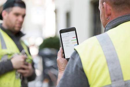 Imagefotografie in der Stadt Bern, Bauarbeiter nutzt die Goana Application auf Handy