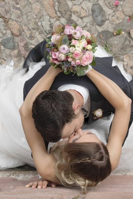 Brautpaar an Mauer, Mann küsst seine Braut zärtlich