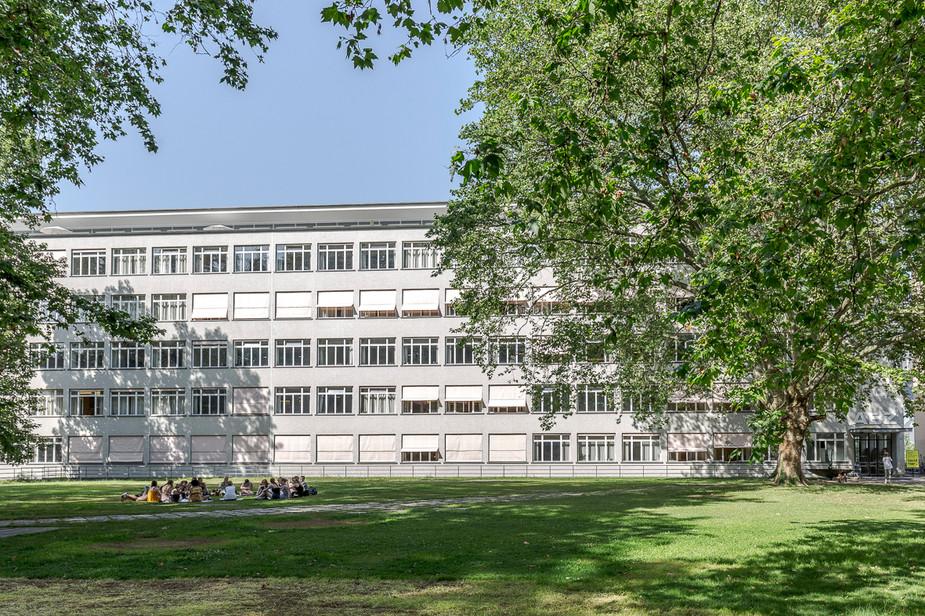 Allgemeine Berufsschule Zürich, Aussen Aufnahme Schulgebäude im Sommer mit Gruppe Schüler auf Wiese
