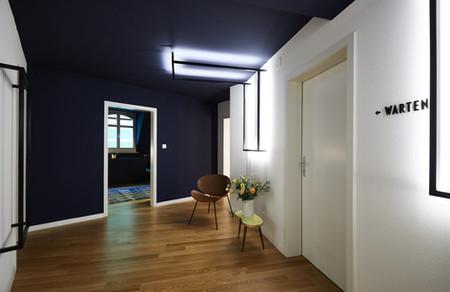 Gang und Wartebereich mit dunkelblauer Wand und Decke, moderner Eingangsbereich Physio Praxis FOI Basel, Architekturfotograf Cartes Fotorafie