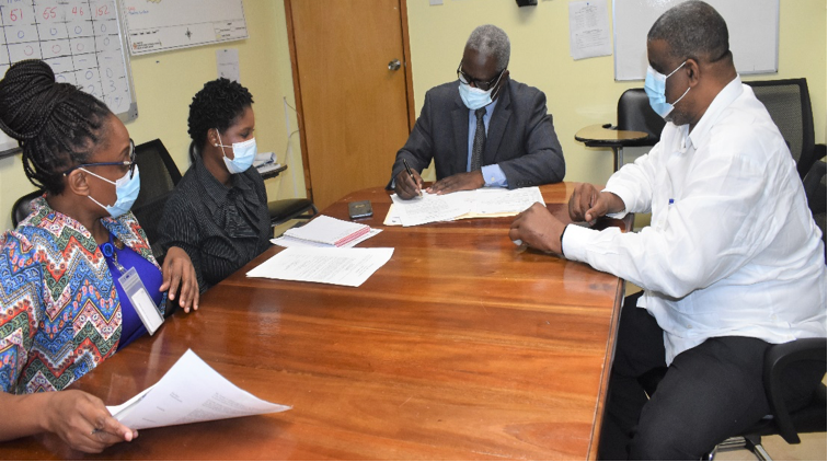 Mr. Wentworth Charles, Board Chairman, SERHA, signs approval for the assumption of duties of Mr. Errol C. Greene to function in the capacity as the Regional Director, SERHA. The signing was held inside the boardroom at the Regional Office on Thursday, July 8, 2021. Looking on from left are: Ms. Pauline Roberts, Director of Human Resources and Industrial Relations, SERHA; Ms. Stacey-Ann Steele, Corporate Secretary/Legal Officer, SERHA and Mr. Errol C. Greene, OD, JP, RD, SERHA