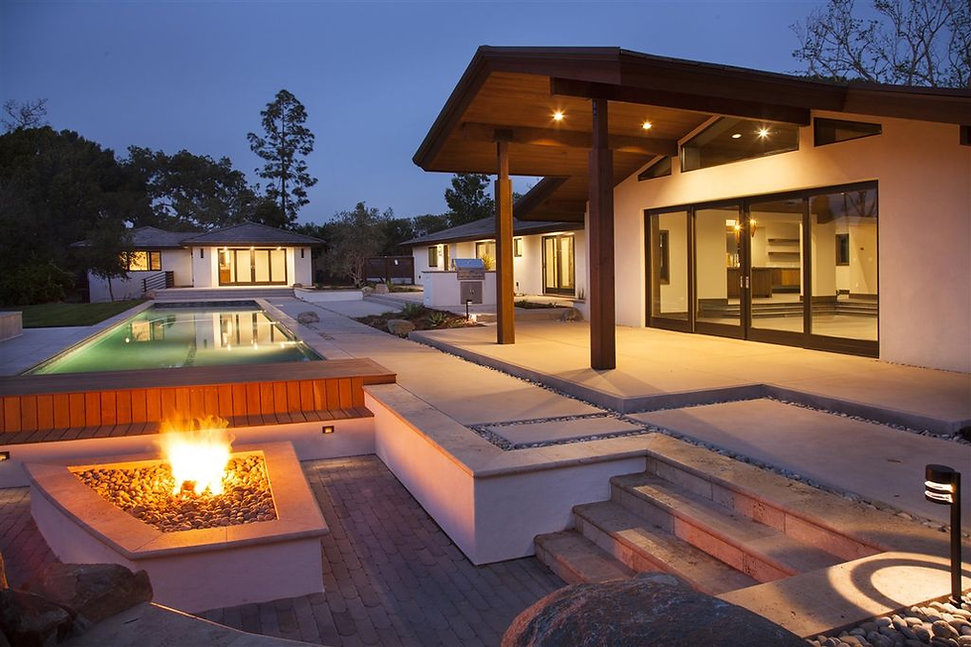 Modern Mid-Century Craftsman interior design by Paschall Design. This is a photo of the exterior of the home with the long pool and unique outdoor firepit and sunken seating area. A beautiful BBQ and landscaping is shown. Guest house is shown in the background.