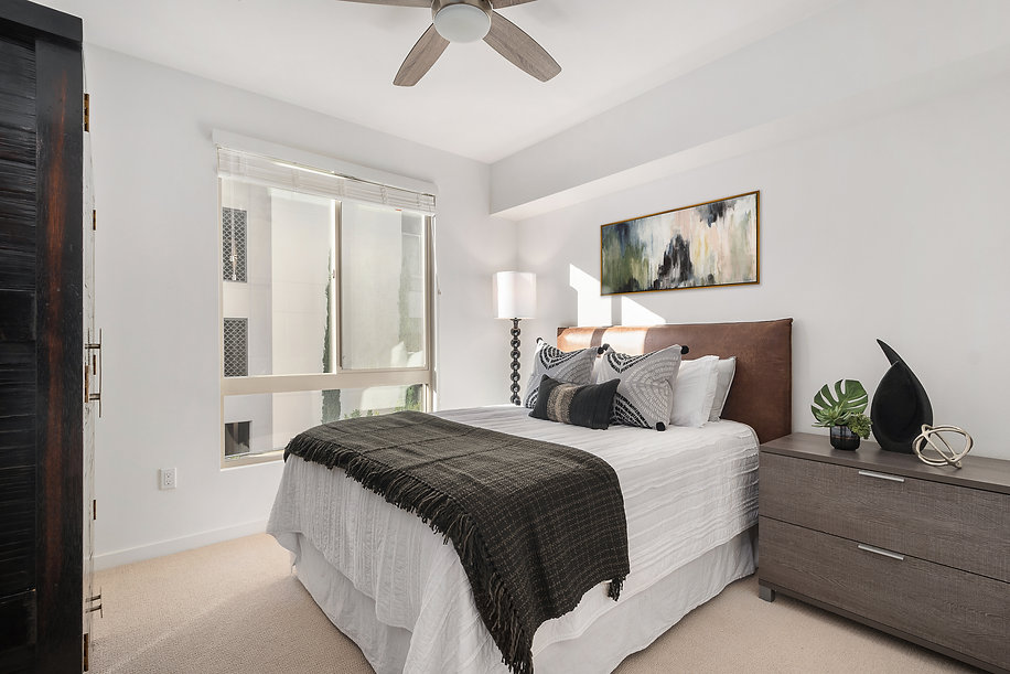Del Mar high rise condo remodel. Interior design by Paschall Design. Here you see the guest bedroom equipped with a new bed, artwork, side tables and more. Accessories include planters, faux plants, and a black rice stone sculpture by Arteriors.