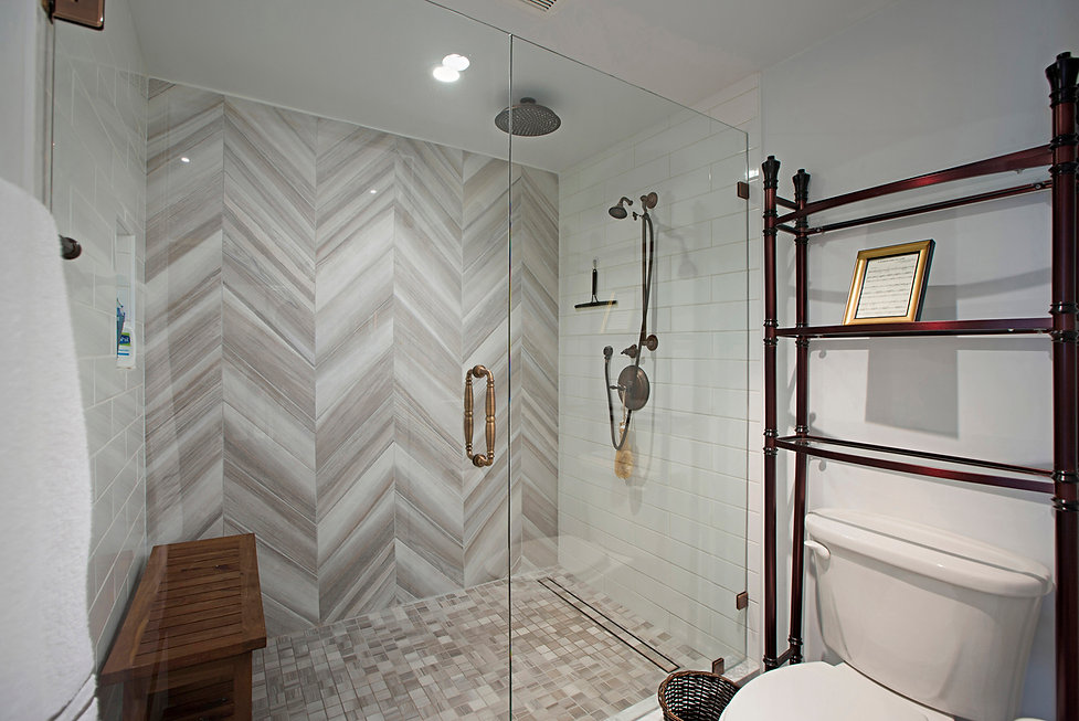 Coastal Del Mar modern glam interior design by Paschall Design. Here you see a modern style bathroom with a grey herringbone tile on the back wall, drawing you in. Oil rubbed bronze shower fixtures and ceiling mounted shower head. White subway tile was specified for the side walls of the shower. A shower bench for seating and hidden drain as also included in the design.