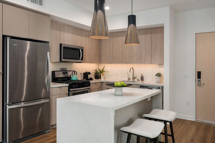 Del Mar high rise condo remodel. Interior design by Paschall Design. Here you see a modern kitchen design with black pendants and white tile. Planters, plants and accessories were also included. The kitchen stools match the bar height table stools in the other room.