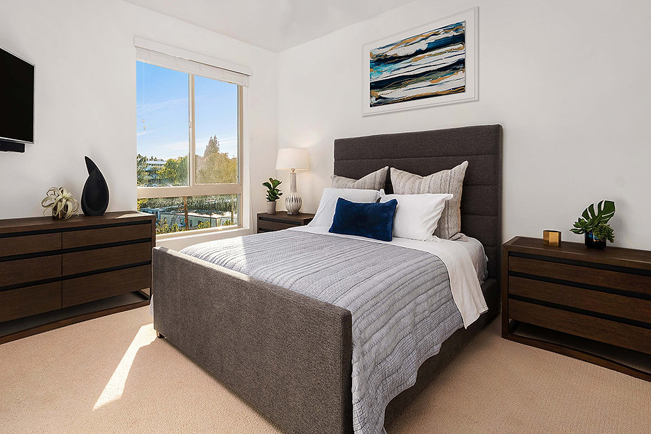 Del Mar high rise condo remodel. Interior design by Paschall Design. Here you see the master bedroom with artwork, bedding, pillows, and more. The bed side tables match the dresser in a dark walnut wood. The TV is mounted above a planter, plant and sculpture.