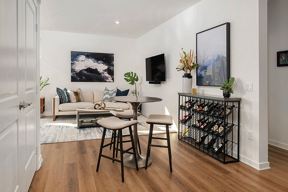Del Mar high rise condo remodel. Interior design by Paschall Design. Here you see a bar height table and stools with a wine rack by four hands in the background. Furniture, sofa, artwork, planter and faux plant selections were included in this design.