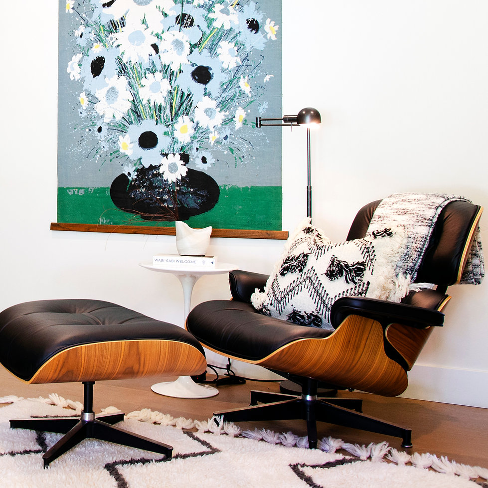 Coastal modern La Jolla interior design by Paschall Design. Black and white pillows sit on top of the Herman Miller chair and ottoman. Flower artwork sits behind along with a white glossy pedestal side table and accessories. A floor lamp for reading was a must.