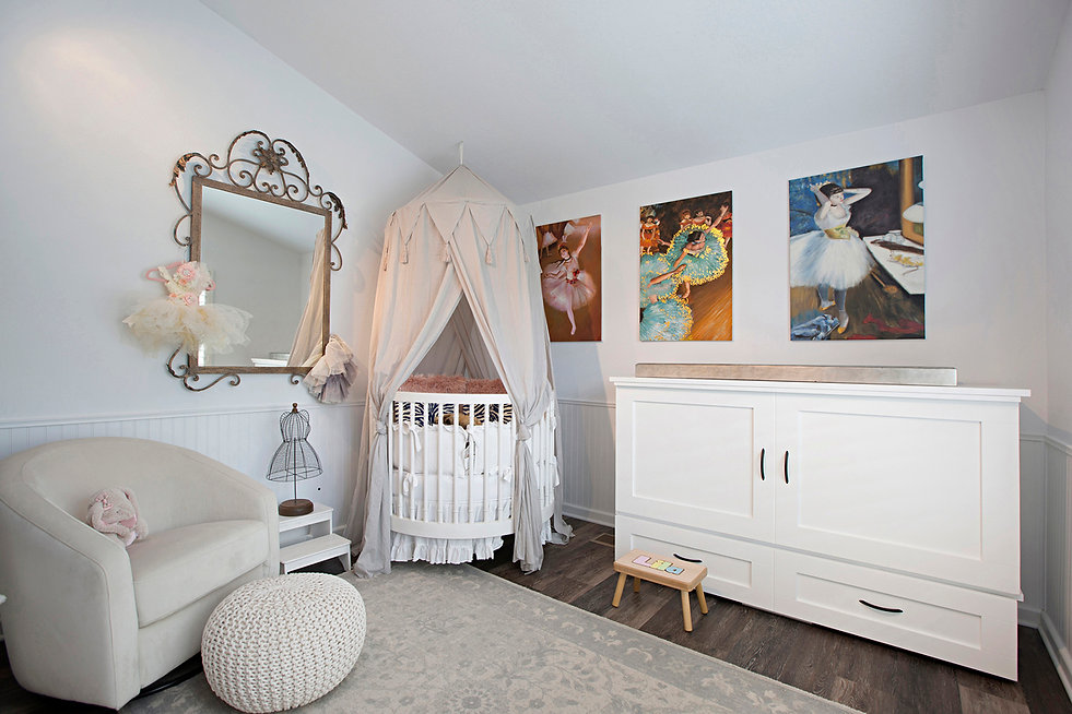 Coastal Del Mar modern glam interior design by Paschall Design. Here you see the nursery, a baby girls dream.  A round crib in the corner of the room is covered by a ceiling mounted crib cover. The lounge chair and footrest was a must for the new mother. Playful, fun, baby, kids room design with ballerina artwork.