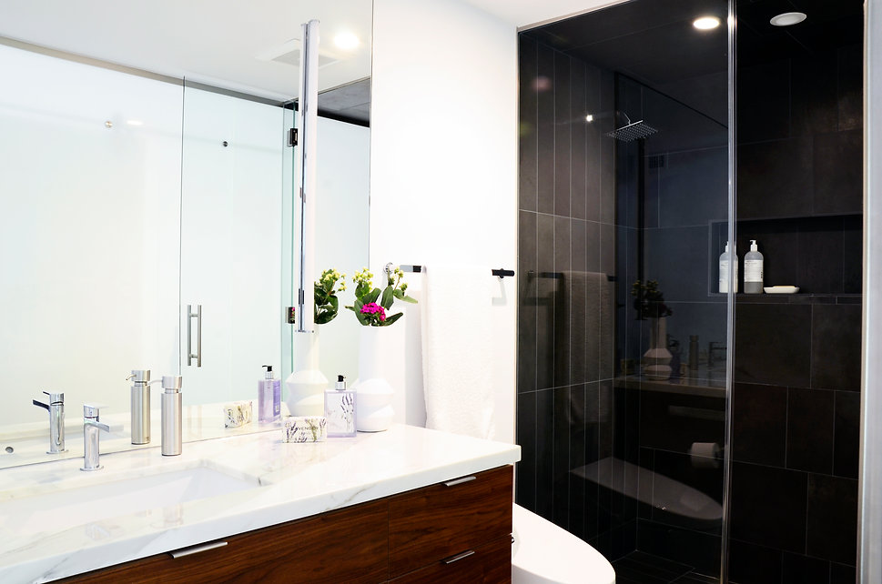 Modern Rancho Santa Fe Remodel. Interior design by Paschall Design. Here you see a modern bathroom with black tile in the shower laid linearly. White marble countertops and teak wood cabinetry. Soap, vases, and more to accessorize.