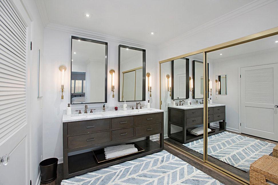 Coastal Del Mar modern glam interior design by Paschall Design. Here you see a modern style bathroom With a blue and white herringbone style rug, black cabinetry, bronze hardware, black steel frame mirrors, and brass sconces. Crystal knobs were used for the closet.