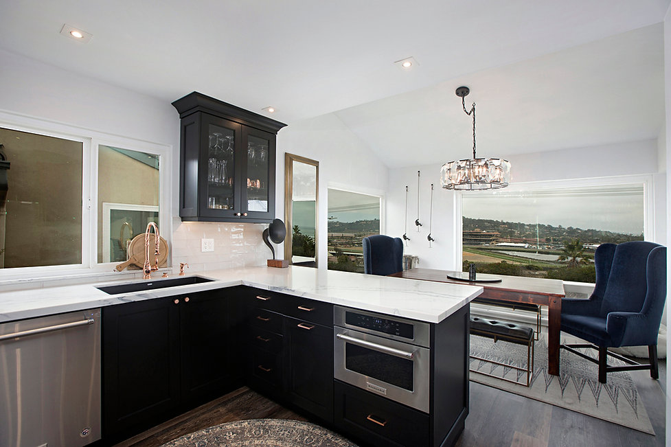 Coastal Del Mar modern glam interior design by Paschall Design. Here you see a modern glam kitchen that includes white subway tile, black cabinetry, marble countertops and stainless steel appliances. Copper faucet, brass hardware, and a black sink.