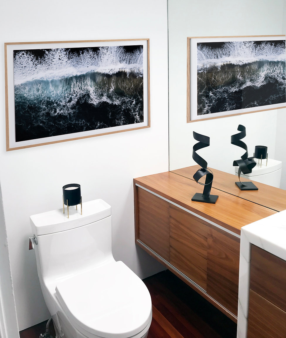 Modern Rancho Santa Fe Remodel. Interior design by Paschall Design. Here you see a modern bathroom with black tile in the shower laid linearly. White marble countertops and teak wood cabinetry. Soap, vases, and more to accessorize. A black sculpture and black artwork contrasted against the white walls.