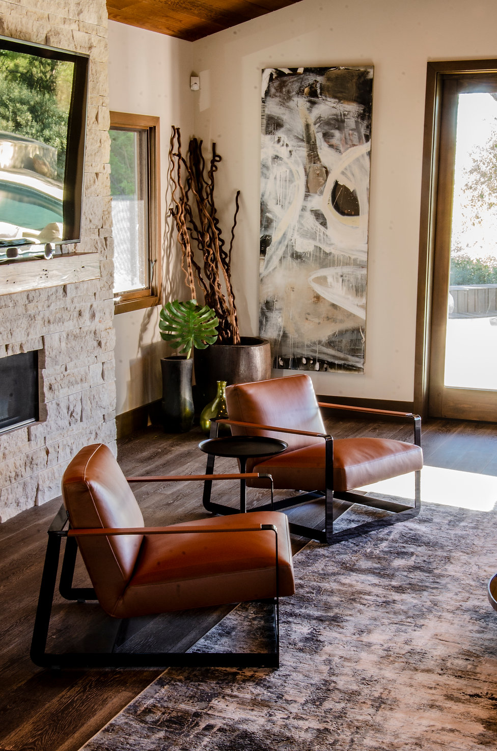 Modern Mid-Century Craftsman interior design by Paschall Design. This is a photo of the living room and entry from another angle. A closeup of the beautiful brown leather modern lounge chairs, with artwork, planters and stone fireplace in the background. Wood trim throughout against sofa white walls. You can see the large rug well in this shot.