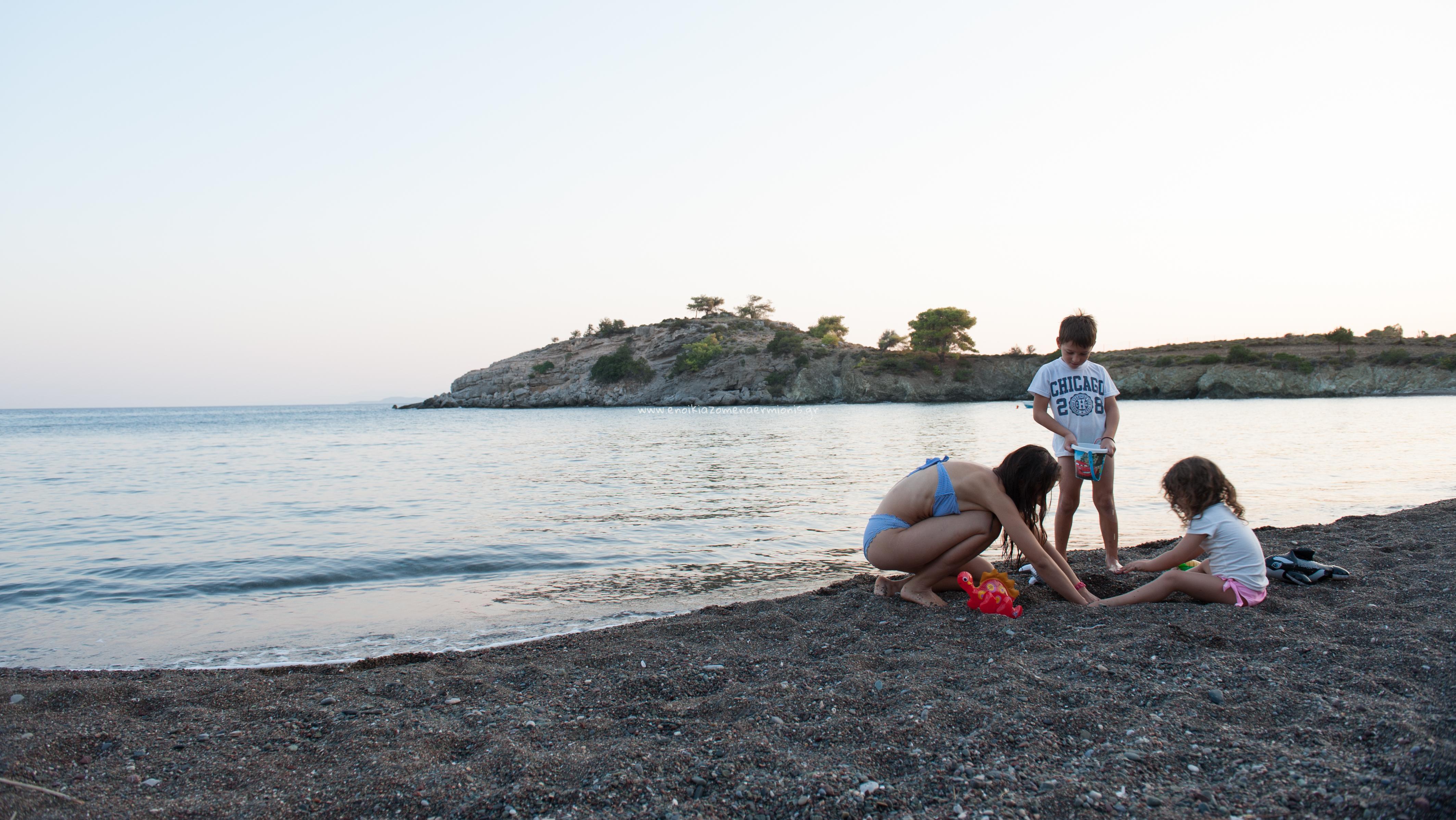 Μάνα & τα παιδιά της παίζουν με κουβαδάκια στην αμμουδιά