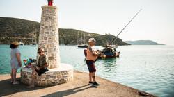 Άντρας ψαρεύει με καλάμι στο μώλο του λιμανιού