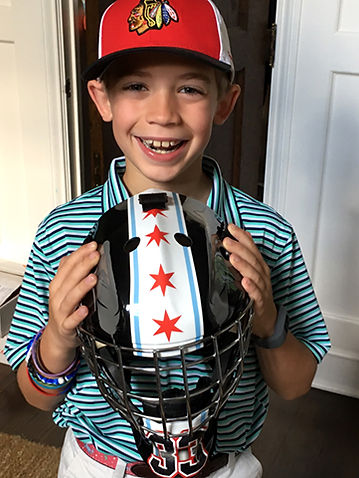 A happy boy with his newly wrapped Bauer goalie mask wrap for the Chicago Jr Blackhawks