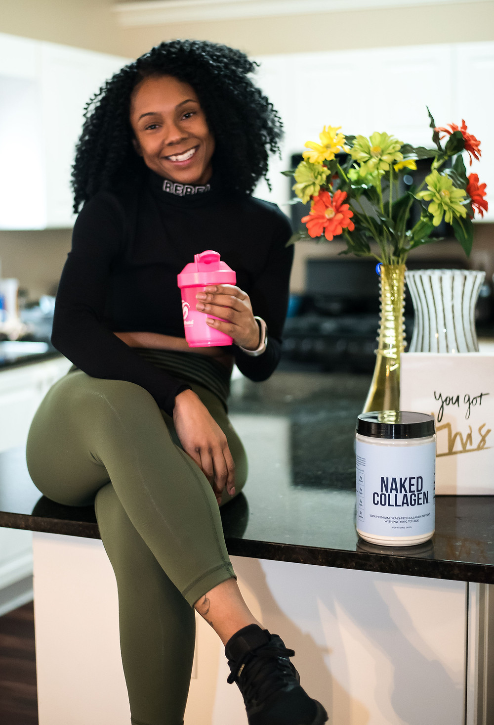 Girl sitting on counter with legs crossed and holding a pink cup while smiling.