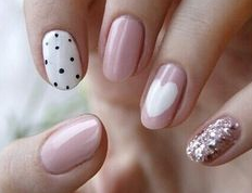 pale pink nails with polka dots and glitter and heart design