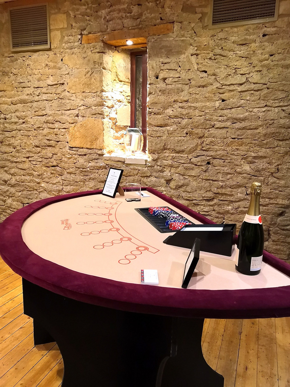 Cream and burgundy blackjack table in converted barn with a bottle of champagne