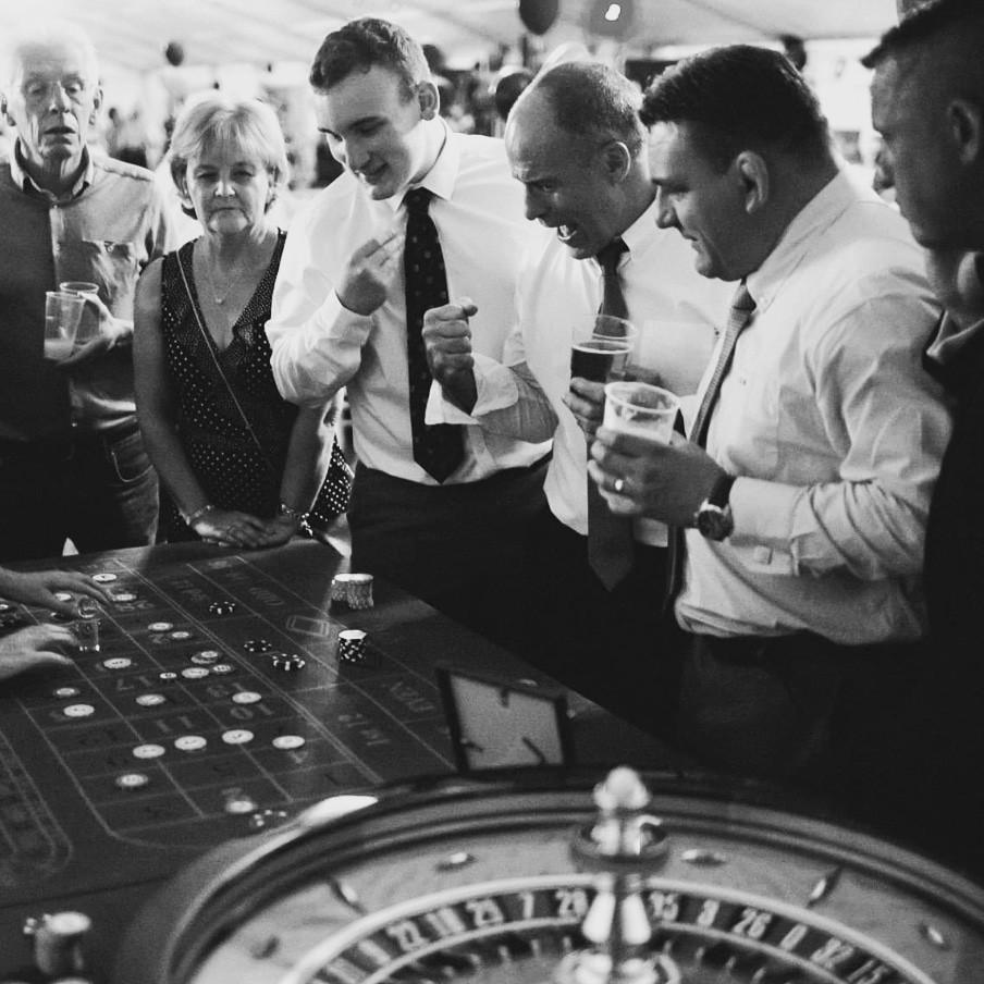 Black and white, men playing roulette cheering, holding beer.