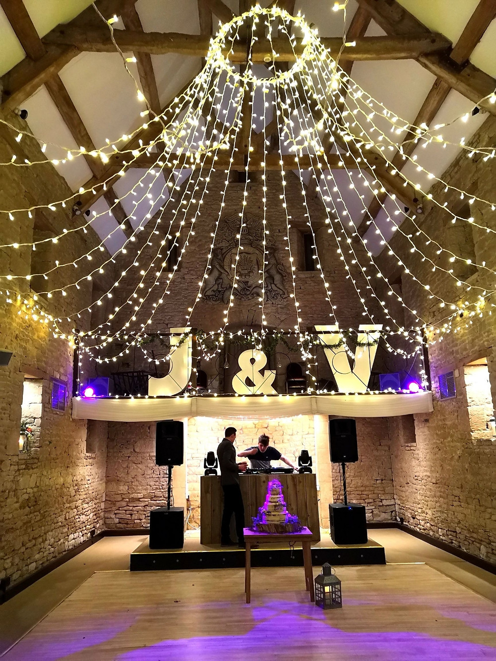 A wedding at the great tythe barn tetbury. fairy lights draped from the ceiling beams with illuminated letters and violet uplightinf